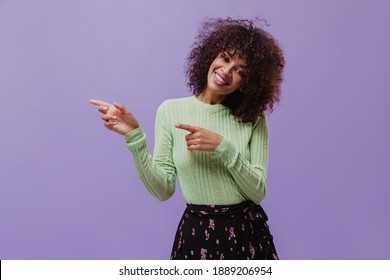 Excited curly brunette woman in green top and dark floral skirt points to left at place for text on isolated purple background.