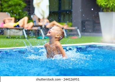 excited cute boy having fun in pool