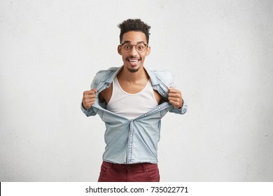 Excited dark skinned male with specific appearance tears off shirt in enjoyment, advertises new t shirt. Man with shaggy hairdo poses in white studio with copy space. People, advertising concept