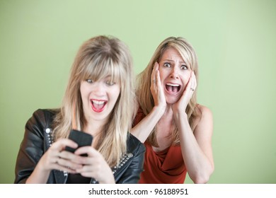 Excited daughter texting with shocked mom behind her over green background