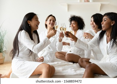 Excited diverse bridesmaid friends wear robes congratulating asian woman bride with wedding bridal shower celebrating birthday getaway bachelorette spa party clinking champagne glasses sitting on bed.