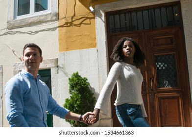 Excited diverse couple of tourist walking in old city. Young man and woman going near old building entrance, looking away in surprise. Outdoor walk concept