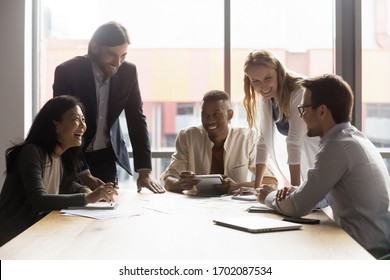 Excited diverse coworkers sit at office desk laugh have fun discussing paperwork at meeting together, overjoyed businesspeople gather at table in boardroom joke smile brainstorming at meeting