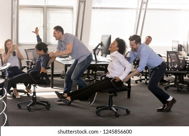 Excited diverse employees having fun together in office, riding on chairs at work, enjoying break, laughing, colleagues shoot video on phone, engaged funny activity, celebrating corporate success