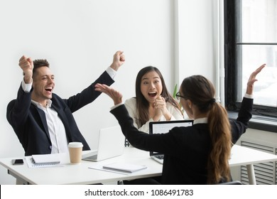 Excited diverse executive colleagues raising hands celebrating unbelievable online result, happy partners motivated by great achievement or team victory, amazed by good news, business success or win