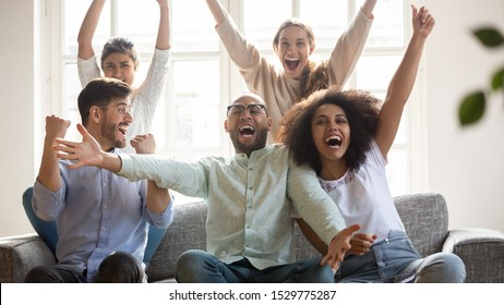Excited diverse football fans celebrating victory, supporting favorite team, screaming with joy, happy friends watching soccer match on tv together, sitting on couch at home, win sport bet