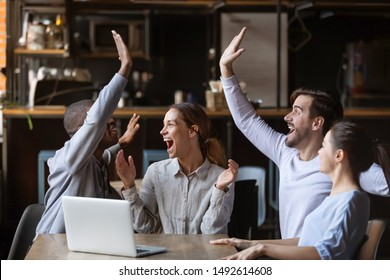 Excited diverse friends celebrate online win watch football game on laptop sit at cafe table together, overjoyed multicultural young football fans supporters happy with victory goal score at party