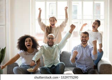 Excited diverse friends celebrating successful football match result, watching tv, sitting on couch at home, football fans screaming with joy, supporting favorite soccer team, win sport bet