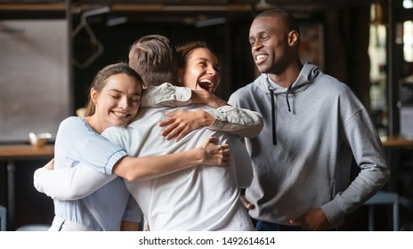 Excited diverse friends embrace greeting male buddy coming at meeting in cafe, multiracial students group hugging guy laughing say hello welcoming at students reunion, multi ethnic friendship concept
