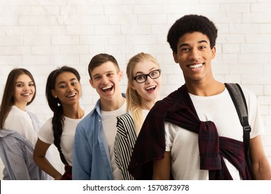 Excited diverse friends standing in line and smiling at camera, posing over white wall