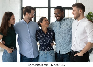 Excited diverse joyful mates colleagues hugging together in office celebrate common project finish, joking enjoy meeting. Corporate party and fun activity, racial gender equality in business concept