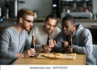 Excited diverse male friends having fun watching football game online video on smartphone drinking beer eating pizza together, three millennial multiracial men having fun cheering favorite sport team
