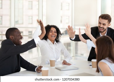 Excited diverse millennial workers give high five celebrate success, happy multiethnic colleagues join hands motivated for shared goal, employees involved in teambuilding activity at meeting