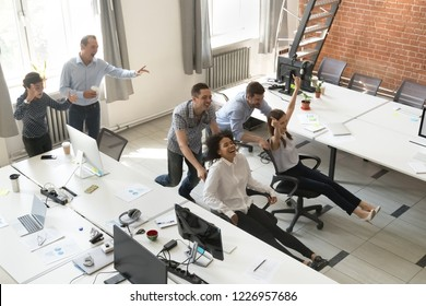 Excited diverse office colleagues having fun riding oh chairs, happy employees enjoy funny competition laughing together feel great at work break, friendly creative team activities concept, top view