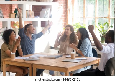 Excited diverse students or employees celebrating success, business achievement, good exam result at meeting, happy African American and Asian team members having fun together in classroom or office