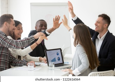 Excited diverse work team giving high five at board meeting, celebrating shared goal achievement, congratulating with win or good result, showing team spirit, unity. Concept of cooperation, rewarding