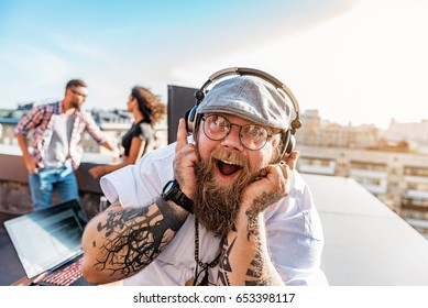 Excited DJ listening to music from earphones
