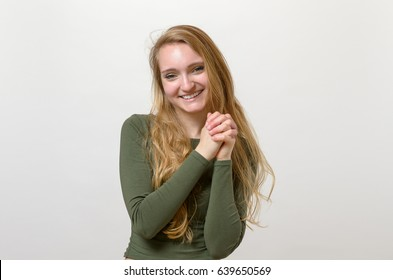 Excited elated young woman clasping her hands with a beaming smile of delight, upper body on white