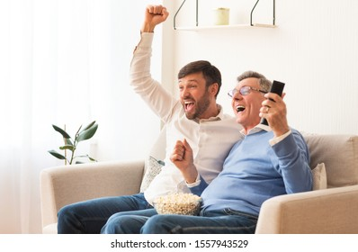 Excited Elderly Father And Middle-Aged Son Watching Sports On TV Shouting Cheering Favorite Team Sitting On Couch Indoor.