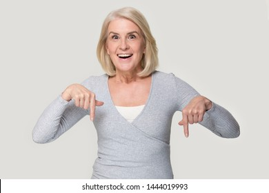 Excited elderly woman head shot showing with her fingers down. Happy smiling old female in years point by finger to bottom looking at camera. Aged person studio portrait isolated on gray background