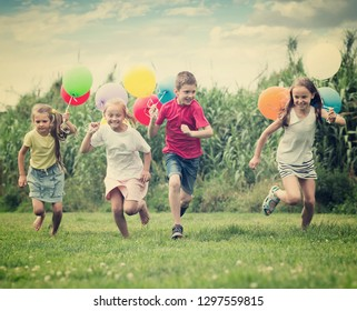 excited elementary school age boy and girls holding air balloons and running in summer park. Selective focus