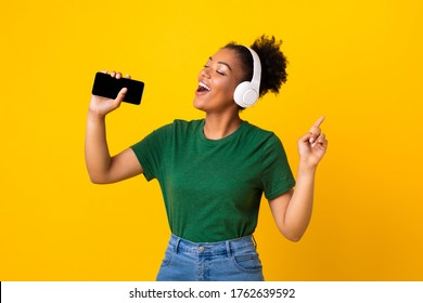 Excited emotional black woman singing her favorite song, using smartphone as microphone, yellow studio background
