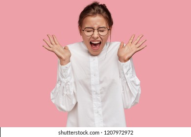 Excited emotional young European woman spreads palms, exclaims very loudly, wears round transparent glasses, dressed in white shirt, poses against pink background. People and emotions concept