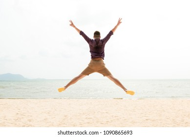 Excited energetic happy tourist man jumping at the beach on summer vacations, fun and freedom concepts