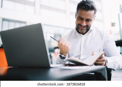 Begeisterte Unternehmer der 40er Jahre in weißem Shirt gekleidet mit Geschäftsergebnissen zufrieden, glücklicher kaukasischer männlicher stolzer CEO mit persönlichem Planer feiert das projizierte Ziel am Sidewalk-Tisch mit Netbook