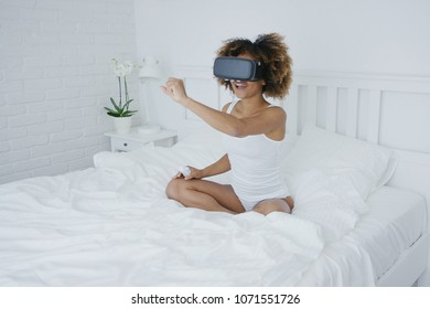 Excited ethnic model with curls posing on bed in glasses of virtual reality and enjoying new world of feelings in morning time.
