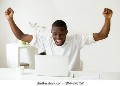 Excited euphoric african winner looking at laptop celebrating online win success achievement result, black man happy about good news, motivated by great offer or new opportunity, got a job promotion