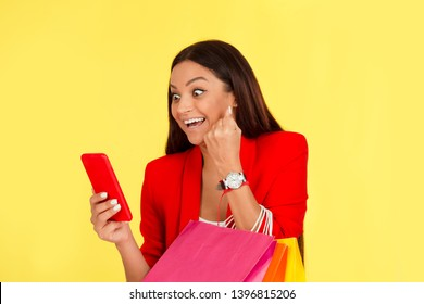 Excited euphoric mid adult woman using smartphone holding shopping bags pumping fist in happiness isolated on yellow background.  Multicultural ethnic model, mixed race Indian African American.