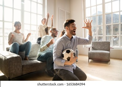 Excited european guy feels happy scream with joy enjoy football team win gather with best multi-racial friends indoors. Group of crazy cheery mates hanging out together celebrating successful tv match