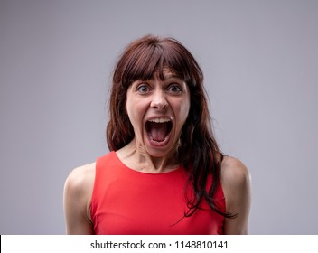 Excited exuberant woman standing screaming at the camera with her mouth wide open isolated on grey