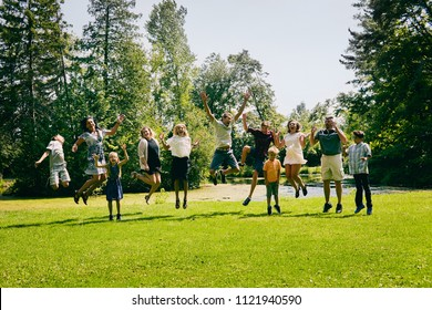 Excited family of eleven jumping in summer park