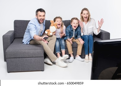 excited family watching tv while sitting on sofa together