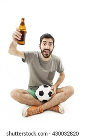 Excited fan holding a ball and beer, cheering. Sitting on floor. Isolated on white background