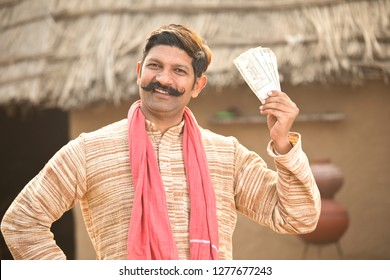 Excited farmer holding Indian rupee notes and screaming