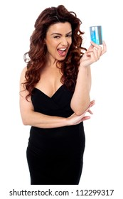 Excited fashionable woman holding cash card isolated against white