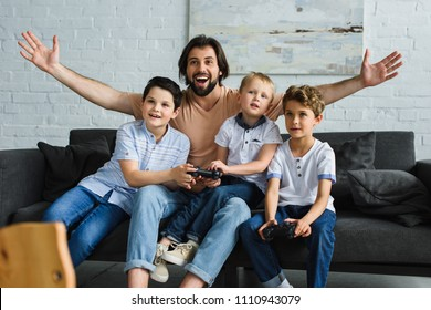 excited father and little sons sitting on sofa and playing video games together at home
