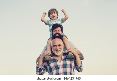 Excited. Father and son playing outdoors. Happy smiling boy on shoulder dad looking at camera. Happy family. Three men generation
