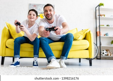 excited father and son playing Video Game on couch in Living Room
