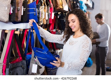Excited female customer purchasing new hand bag in store