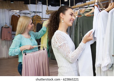 Excited female customers looking for new garments at the store