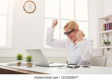 Excited female doctor looking at laptop, celebrating success. Unexpected news or medical tests results. Medicine and healthcare, online diagnostics concept, copy space