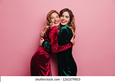 Excited female friends huggs on pink background. Indoor photo of blithesome adult sisters posing with smile.