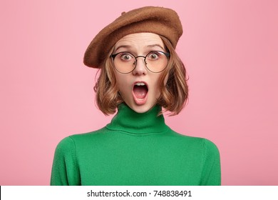 Excited female nerd wears beret and spectacles, looks surprisedly into camera, shocked to loose competition, being sure in her knowledge and results. Fearful young pretty woman afraid of darkness