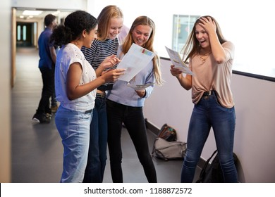 Excited Female Teenage High School Students Celebrating Exam Results In School Corridor