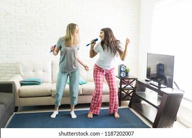 Excited females enjoying karaoke during pajama party at home