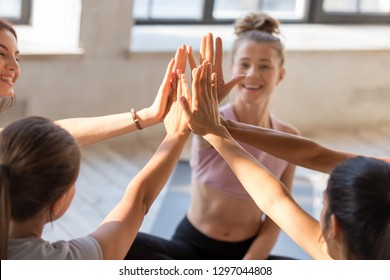 Excited fit female yogi give high five sitting in circle motivated after successful yoga session together, happy women engaged in teambuilding, join hands for shared goal or success at training